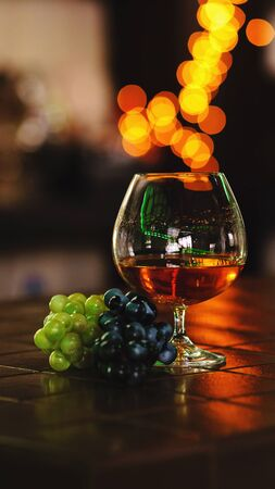 French grape brandy, strong alcoholic drink. Still life. Glass of cognac and bunch of grapes. Service and tasting concept. Stok Fotoğraf - 128453108