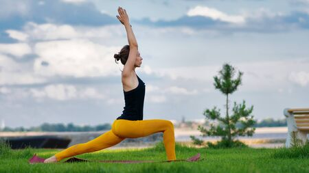 Young woman with trim figure practicing yoga warrior pose. Girl performs yoga in a park on International Yoga Day. Yoga helps find balance. Practice asana outdoor. Stock Photo