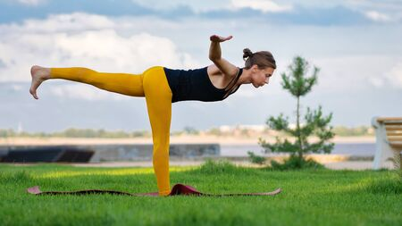 Young woman with trim figure practicing yoga warrior pose. Girl performs yoga in a park on International Yoga Day. Yoga helps find balance. Practice asana outdoor. Foto de archivo - 128453557