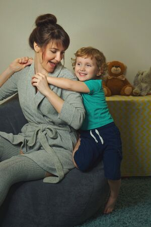 Stylish mother with a charming little son spend time in the childrens room. Stock Photo