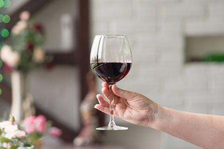 Femme main tenant un verre de vin sur fond naturel flou. Espace pour le texte. Dégustation de vins, restaurant, oenotourisme. Concept de boissons alcoolisées.