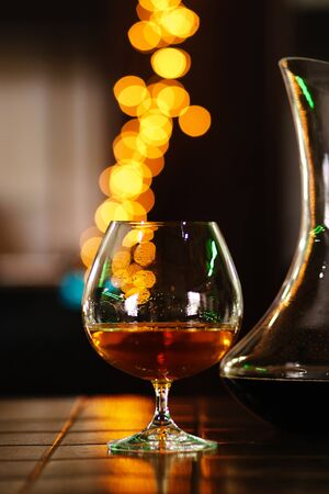 Snifter of brandy in elegant glass with space for text on dark colorful background. Decanter defocussed. Traditional French drink. Stiff drink. Service and tasting concept. Stok Fotoğraf