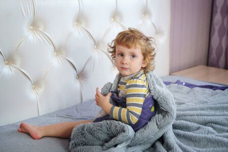 Portrait of a charming baby with golden hair and clear blue eyes. Angel face. Boy sits on the parents bed in the bedroom. Pranks time Stock Photo