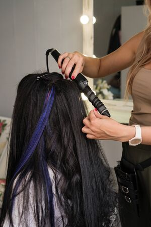 Hairdresser makes hairstyle to client. Hairdressing services. Creating hairstyle. Hair styling process. Beauty service concept