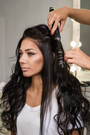Hairdressing services. Creation of evening hairstyles fashionable stylish women's hairstyles. Hair styling process. Curls. Courses in hairdressing. Training hairdressing.  Beauty industry. Foto de archivo