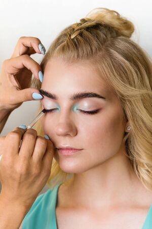 Makeup artist applies eye shadow on moving eyelid model. Creative makeup. Beauty industry. Beauty salon concept