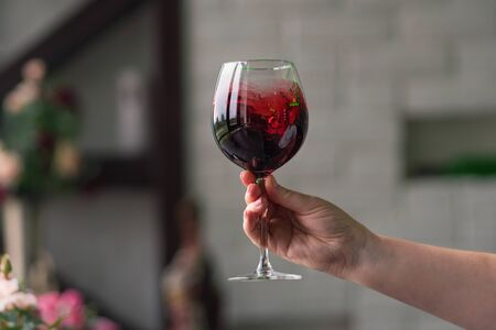 Hand sommelier holding glass of red wine. Swirling wine glass in wine tastings  Red wine concept. Wine tour. Space for text.