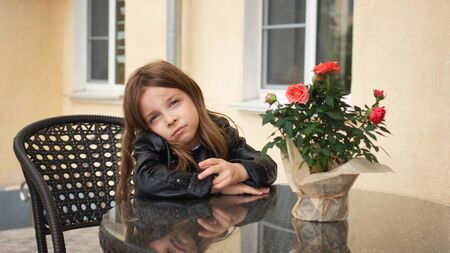 Fashionable little schoolgirl sitting at table of summer terrace of restaurant. She's upset about waiting for order. Фото со стока