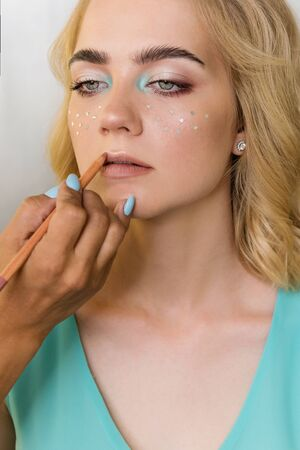 Make-up artist encircles contour of sensual lips with lip liner. Healthy hair, hairstyle, makeup, cosmetics, beauty salon concept. Healthy complexion, ideal skin. Beauty industry Banco de Imagens