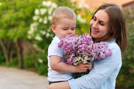 Junge liebevolle Mutter, die mit ihrem kleinen Sohn auf Frühlingshintergrund geht. Nettes Kind und ihre Mutter im Freien. Genießen Sie das schöne Wetter und die Frühlingsblumen. Glück, ein Elternteil zu sein. Zeit zusammen.