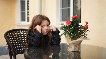 Fashionable little schoolgirl sitting at table of summer terrace of restaurant. Shes upset about waiting for order. Reklamní fotografie