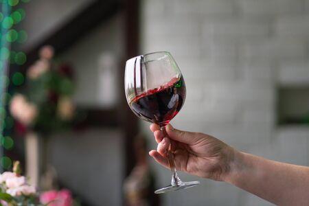 Sommelier à main tenant un verre de vin rouge. Verre à vin tourbillonnant dans les dégustations de vin Concept de vin rouge. Visite des vins. Espace pour le texte.