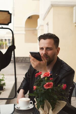 Stylish hipster freelancer drinking coffee on a summer terrace of a restaurant. A man is recording a voice message. Handsome guy with a fashionable haircut and neat beard