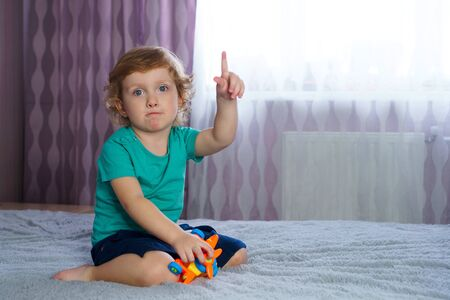 Golden-haired charming baby points finger up. Idea for the game. Interesting pastime alone. 스톡 콘텐츠