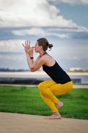 Young beautiful woman practicing yoga with cloudy sky in the background. Wellness concept. Calmness and relax, woman happiness. Yoga is the best holistic workout. Mental and physical health. Foto de archivo - 129207942