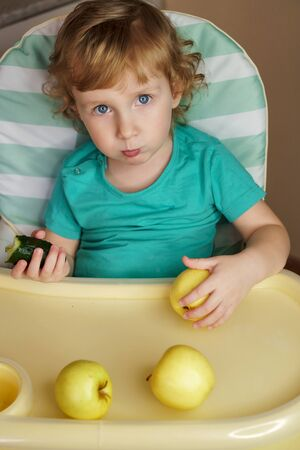 Portrait of a charming baby with golden hair and clear blue eyes. Angel face. Toddler eats apples sitting behind the highchair. Concept of proper nutrition for the health of the baby.