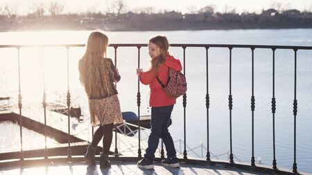 Two young schoolgirls are having confidential conversation. They stand on observation deck and see wooden pier. Sunny evening. Urban casual outfit. Relaxing outdoors. Happy childhood, lifestyle