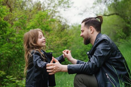Modern stylish family walking in the park. Cute little daughter is calling dad to play. Time together. Family look. Urban casual outfit. Fatherhood makes life more livable Stock Photo