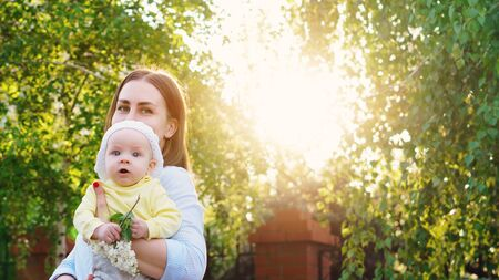 Young loving mother walking with her little baby on spring background. Cute child and her mom outdoor. Happiness to be a parent. Time together. 스톡 콘텐츠