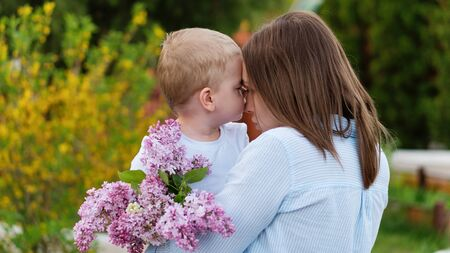 Young loving mother walking with her little son on spring background. Cute child and her mom on outdoor. Enjoy the good weather and spring flowers. Happiness to be a parent. Time together. Foto de archivo