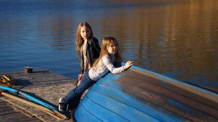 Charming children schoolgirls spending time by lake. Two kids playing on wooden pier. Fall weekend in open air. Leisure activity during sunny day. Active family time on nature. Hiking and adventure