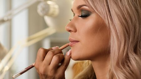 Beautiful well-groomed girl with gorgeous shiny hair in beauty salon. Makeup artist draws contour of pouty lips with lip liner. Healthy hair, makeup, cosmetics, hair styling.