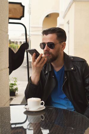 Stylish hipster freelancer over a cup of coffee on a summer terrace. Man record voice messages at work. Handsome guy with a fashionable hairstyle and stylish beard Фото со стока