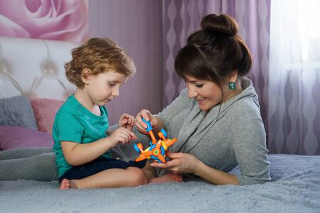Stylish mother with a charming little son spend time together in the bedroom. Mom with baby play toys on the parent's bed. Having fun together. Interesting pastime Фото со стока - 129214241