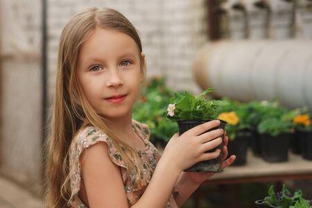 Scolaro allegro che tiene il vaso con la pianta in fiore nelle mani in aranceto. Escursione in serra. Moda ragazza estiva. Infanzia felice. Bellezza naturale. Giorno dei bambini. botanico. giardino fiorito