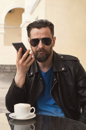 Portrait with warm tinted stylish fashion hipster. Man with fashionable hairstyle and beard in sunglasses holds smartphone in his hand. He went to cafe for a cup of coffee between business meetings.