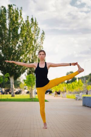 Handsome athletic woman doing yoga asanas in the park. Enjoy pilates. Girl do muscle stretching. Sylph woman.  Health care. Achieving success in sport. Sport and fitness. Success is no accident. Stock Photo