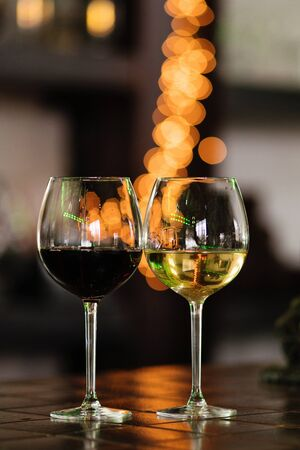 Two glasses of wine white and red standing on a table. Colorful bokeh. Wine tastings, wine tour. Warm toning. Concept alcoholic drinks. Stok Fotoğraf