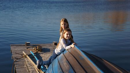 Charming children schoolgirls spending time by lake. Two kids playing on wooden pier. Fall weekend in open air. Leisure activity during sunny day. Active family time on nature. Hiking and adventure Banque d'images