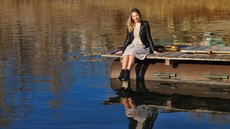 Stylishly dressed attractive girl spends last warm autumn days in nature. She is resting on wooden pier by the lake. Catch sun's rays. Hiking and adventure. In harmony with yourself. Lifestyle concept