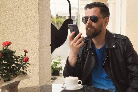 Stylish hipster freelancer over a cup of coffee on a summer terrace. A man is viewing the news feed of social networks in his smartphone. Handsome guy with a fashionable haircut and stylish beard