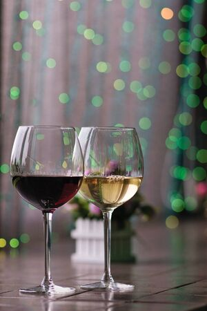 Two glasses of wine white and red standing on a table. Colorful bokeh. Wine tastings, wine tour. Cold toning. Concept alcoholic drinks. Stok Fotoğraf