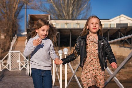Children are walking wooden pier on lake. Two cute sisters have fun relaxing. Leisure activity during sunny day. Active family time on nature. Hiking and adventure. Happy childhood, lifestyle concept
