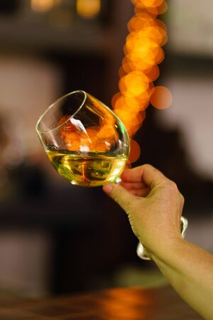 Hand sommelier holding glass of white wine. Wine-tasting. White wine concept. Wine tour. Vertical, warm toning