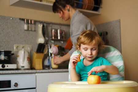 Adorable little baby eating dessert in the kitchen. He sits in a highchair. Mom in the background defocusing the dishes. Weekday young family. Maternity leave. Holiday to care for the child 스톡 콘텐츠