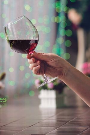 Hand sommelier holding glass of red wine. Glass of red wine on background of colorful bar. Bokeh. Cold toning. Space for text. Concept alcoholic drinks. Stok Fotoğraf - 129214592