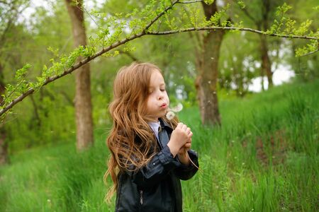 Cute stylishly dressed girl schoolchild blowing on a dandelion. Summer is coming soon. Space for text