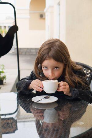Stylish little schoolgirl enjoys delicious coffee on the summer terrace of the restaurant. Coffee break.