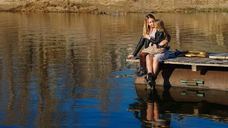 Fashionable stylish family for a walk. Mom and daughter sits on a wooden pier near the lake. Happiness to be a parent. Family look. Relaxing outdoors. Ampaigns and adventures. Lifestyle concept.