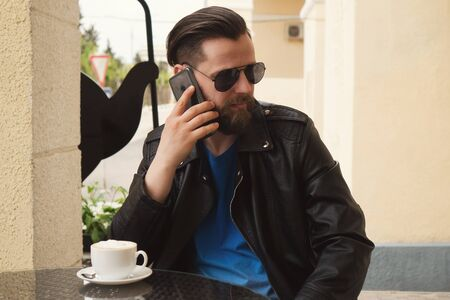 Stylish hipster freelancer over a cup of coffee on a summer terrace. A man solves work issues by phone. Coffee break. Handsome guy with a fashionable haircut and stylish beard