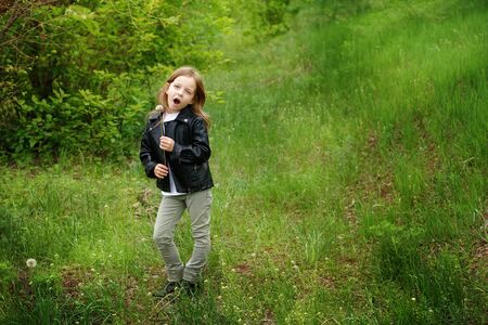 Fashionable girl, schoolchild plays in the park. She imagines that dandelion is microphone and sings. Summer is coming soon. Green meadow. Place for text. Stock Photo