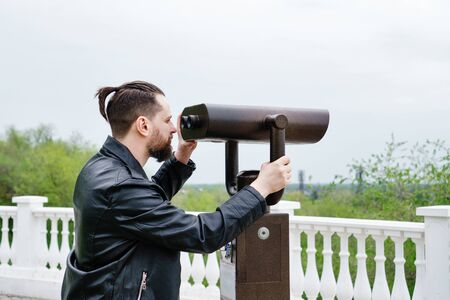 Modern stylish man looking in stationary binoculars from the observation deck. Concept of tourism, travel and sightseeing