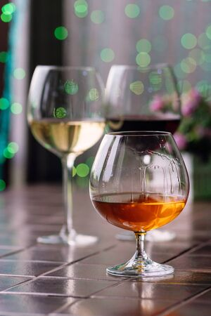 Brandy in typical snifter. Cognac in elegant glass with space for text on colorful background. Two glasses of wine in background unfocus. Tasting, restaurant. Concept alcoholic drinks.