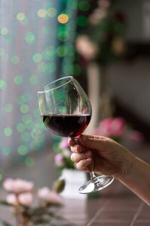 Hand sommelier holding glass of red wine. Glass of red wine on background of colorful bar. Bokeh. Cold toning. Space for text. Concept alcoholic drinks.