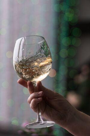 Sommelier à la main tenant un verre de vin blanc. Verre à vin tourbillonnant dans les dégustations de vin Concept de vin blanc. Visite des vins. Virage vertical à froid