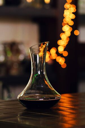 Decanter with red wine stands on bar of restaurant. Colorful bokeh. Wine tastings, wine tour. Warm toning. Concept alcoholic drinks.